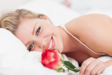 Blue eyed woman smiling with a rose in a bed photo