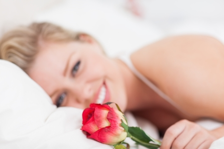 Young woman holding a rose in a bed photo