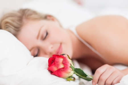 Young woman with a rose sleeping in a bed photo