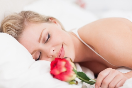 Smiling woman with a rose sleeping in a bed photo