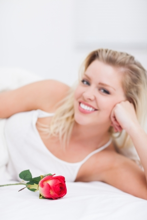 Young woman with a rose smiling on her bed photo