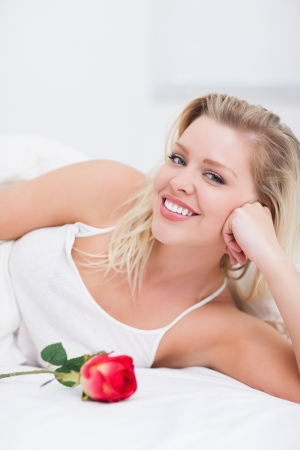 Woman with a rose smiling on her bed photo