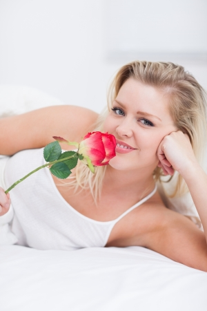 Young woman smelling a pink rose on her bed photo