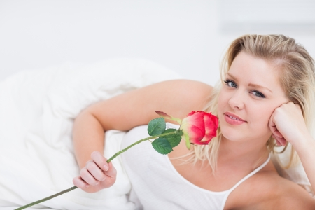 Young woman holding a pink rose while lying on her bed photo