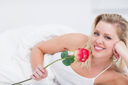 Young woman holding a pink rose while lying in her bed photo
