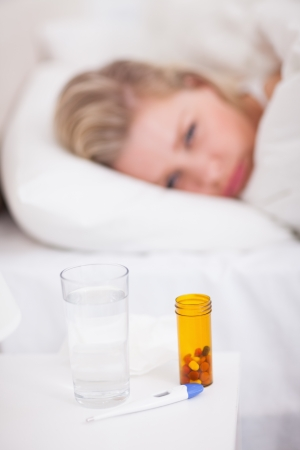 Medicines and thermometer on a beside table with a woman in her bed Stock Photo - 16202066