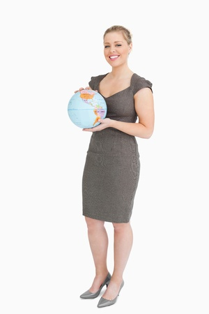 Businesswoman holding a globe against white background photo