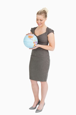 Woman looking at a globe against white background photo