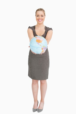 Businesswoman showing a globe against white background photo