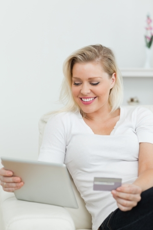 Casual woman using a tablet pc for e-commerce on a sofa photo