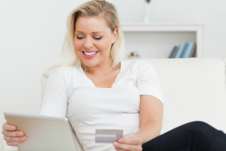 Casual woman sitting on the sofa using a tablet pc on the sofa photo