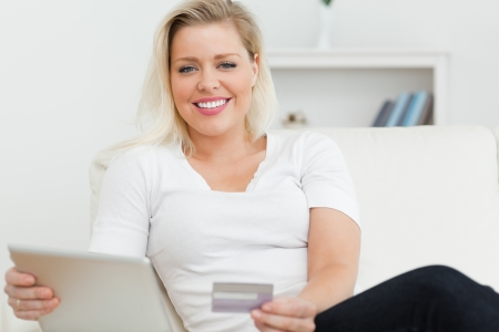 Casual woman with tablet pc and a credit card in a living room photo