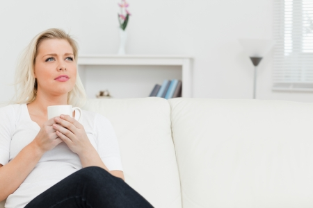 Woman sitting on the sofa with cup in her hands in living room Stock Photo - 16202604