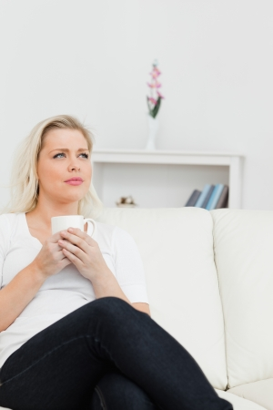 Woman with a cup of coffee in her hands on a sofa Stock Photo - 16203016