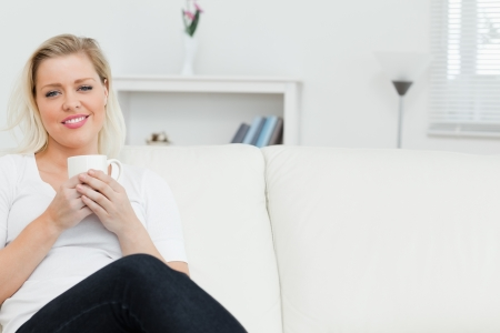 Woman on a sofa drinking a coffee in a lounge Stock Photo - 16202778
