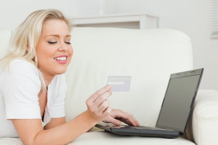 Woman with a credit card and a laptop while lying on a sofa photo