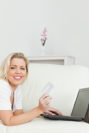 Woman purchasing online while lying on the sofa photo