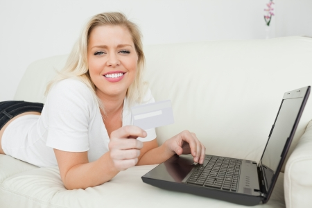 Casual woman lying on a white sofa with a credit card and a laptop photo