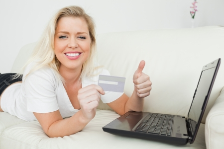Woman lying with a thumb up and a credit card using a laptop  photo