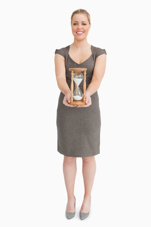 Woman holding a hourglass against white background photo