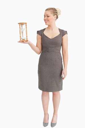 Woman holding in her hand a hourglass against white background photo