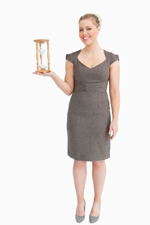 Woman holding a hourglass in her hand against white background photo
