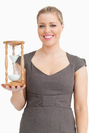 Woman smiling while holding a hourglass against white background photo
