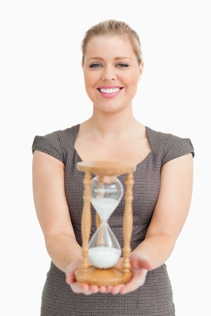 Woman showing a hourglass against white background photo