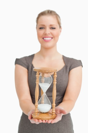 Woman smiling showing a hourglass against white background photo