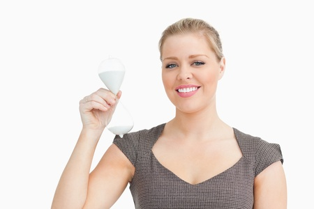 Woman having a hourglass against white background photo