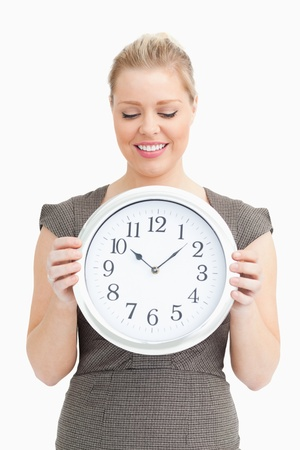 Woman looking at a clock in her hands against white background Stock Photo - 16204186