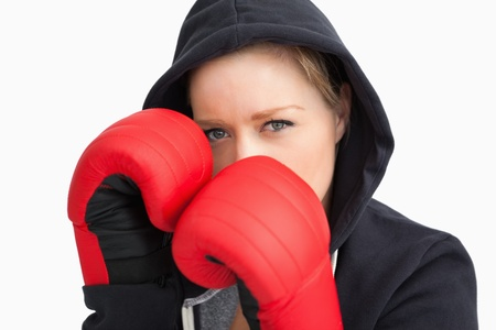 Woman with hoodie boxing against white background photo