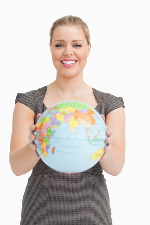 Woman showing a globe against white background photo