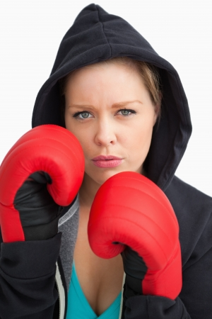 Woman showing her boxing gloves against white background photo