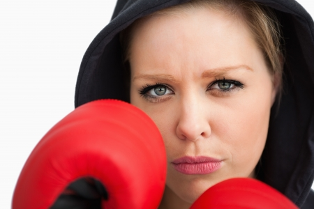 Woman protecting her face with boxing gloves against white background photo