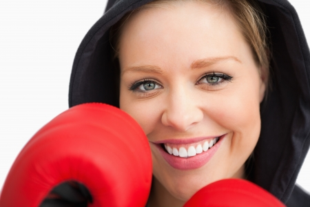 Woman smiling boxing against white background photo