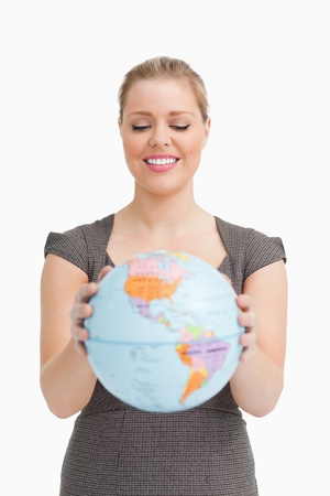 Pretty woman showing a globe against white background photo