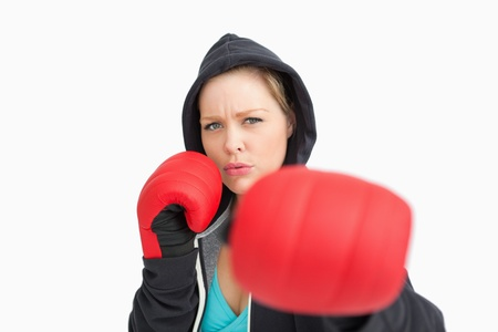 Woman with gloves hitting against white background photo