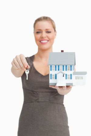 Woman showing a key and a model house against white background photo