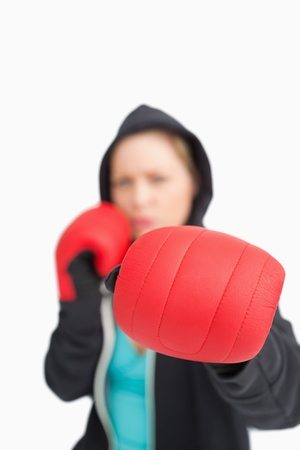 Woman boxing with a red gloves against white background photo