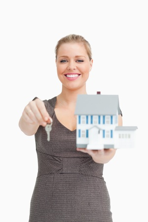 Woman smiling showing a model house and a key against white background Stock Photo - 16203593