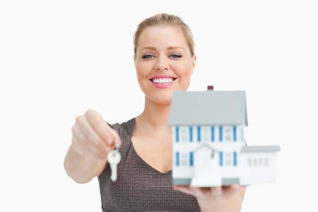 Model house and a key holding by a woman against white background Stock Photo - 16201461