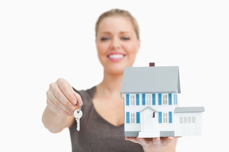 Woman blurred showing a model house and a key against white background Stock Photo - 16200714
