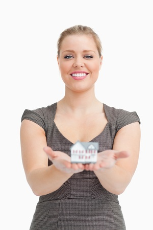 Smiling woman showing a model house against white background Stock Photo - 16204451