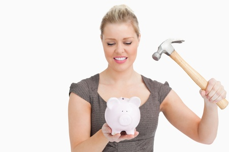 Woman wanted to break a piggy bank against white background photo