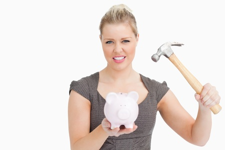 in need of space: Woman want break a piggy bank with a hammer against white background