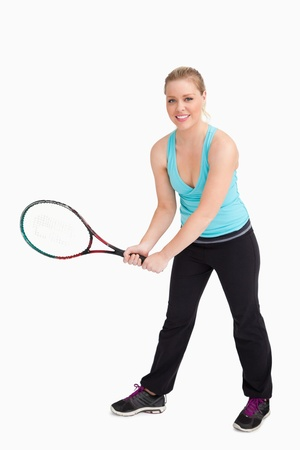 Woman holding a racquet with her two hands against white background photo