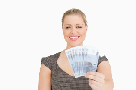 Woman smiling showing euros banknotes against a white background Stock Photo - 16201370