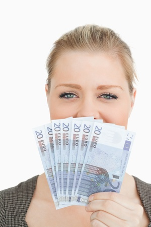 Woman hiding a middle of her face with euro banknotes against white background photo