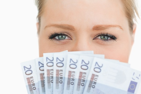 Close up of a woman face hidden with euro banknotes against white background photo
